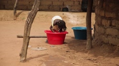 African kid washing while villagers stroll on native village in Guinea Bisseau - stock footage