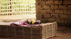 west Africa - kid sleeping native village - stock footage