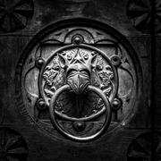 Antique door knocker shaped monster's head. - stock photo