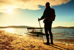 Stock Photo of Tall tourist walk on beach at paddle boat in the sunset