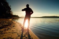 Sportsman  running at amazing summer sunset along coastline in sport and heal Stock Photos