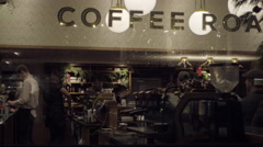 Coffee house with baristas and customers inside through glass window with sign Stock Footage