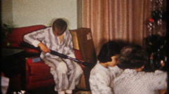 3054 young boy gets a gun & watch for Christmas - vintage film home movie Stock Footage