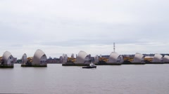 Small boat passing the river Thames barrier, London Stock Footage