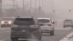 Snow flurries blowing snow and traffic on city streets Stock Footage