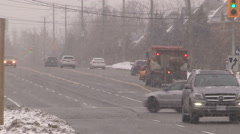 Snow flurries blowing snow and traffic on city streets - stock footage