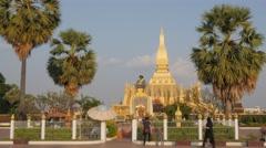 Tourists making photgraph at King Setthathirat statue That Luang,Vientiane,Laos Stock Footage