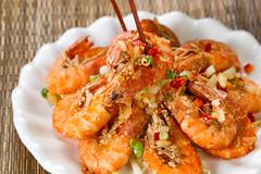 Fried bread coated shrimp and garnishes on white serving plate ready to eat - stock photo