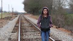 Sad Teen Girl with Earphones and Hoodie Standing on Train Tracks - stock footage