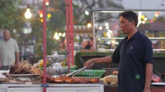 Man barbecuing meat at riverside restaurant,Vientiane,Laos - stock footage