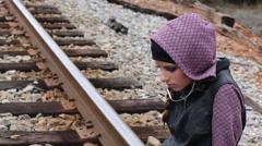 Sad Teen Girls Hangs Head while Sitting on Railroad Tracks - stock footage