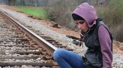 Pretty Teen Girl Sits on Train Tracks and Looks Sad - stock footage
