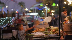 Boy helping mother with keeping food clean,Vientiane,Laos Stock Footage