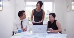 Three Asian coworkers brainstorming a project together in the boardroom. Shot on Stock Footage