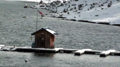 Stock Video Footage of Boat Shack and Docks on Snowy Mountain Lake