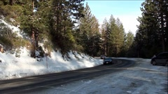 Line of Cars Driving Down Icy Snowy Mountain Road - stock footage