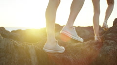 Couple walking to exploring a rocky coastal point with sun flaring Stock Footage