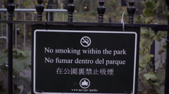 close-up of no smoking within park sign in both English and Spanish, NYC - stock footage