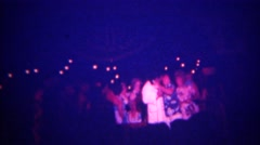 1973: Women kissing and hugging sleazy entertainer after pop music performance.  - stock footage