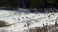 Crowds of People Playing at Lakeside Snow Park Stock Footage