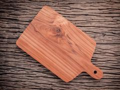 Empty vintage Teak wood cutting board on grunge wood food background concept. Stock Photos