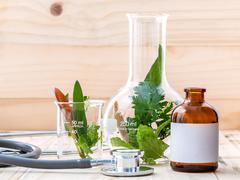 Alternative health care fresh herbal in laboratory glassware  with  stethosco - stock photo