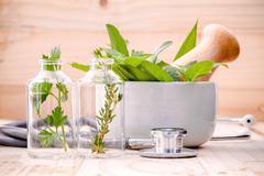 Alternative health care fresh herbal in laboratory glassware  with  stethosco - stock photo