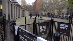 Panning shot of big dog run entrance on cold fall day Washington Square Park NYC Stock Footage
