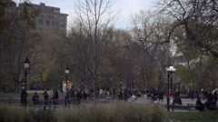 Panning shot across Washington Square Park from grass to famous arch on cold NYC Stock Footage