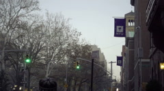 Tilting down establishing shot of NYU street flag overhead Greenwich Village NYC Stock Footage