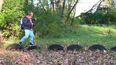Little boy with big backpack goes on tires by wheels Stock Footage