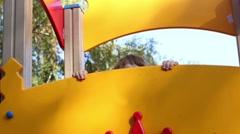 Little girl peeking fun on playground in autumn day Stock Footage