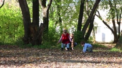 Little girl and boy with his mother throw up leaves in park in autumn day Stock Footage
