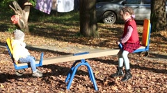 Girl in a red vest goes for a drive on seesaw with his little sister Stock Footage
