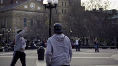 Two guys playing punchball game back and forth in Washington Square Park in NYC Stock Footage