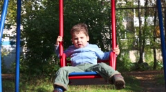 Little boy goes for drive on swing in warm autumn day Stock Footage