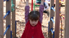 Little girl in red vest playing on playground in autumn day Stock Footage