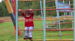 Happy little boy climbs on ladder on playground at summer day Stock Footage
