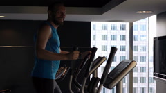 Portrait of happy man exercising on elliptical machine in gym, super slow motion Stock Footage