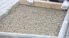 Leveling gravel a wooden board Stock Footage