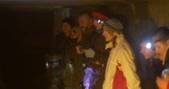 Group of a Tourists With Head Lamps Are Standing in a Line at The Cave Wall Stock Footage