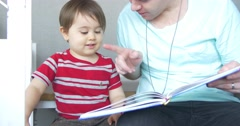 Father and son reading story time book together as family moving shot 4K Stock Footage
