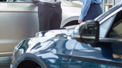 Salesperson representing a vehicle to his customer - stock footage
