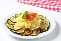 circle of roasted zucchini slices with potatoes and fried eggs - stock photo