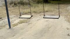 Two empty swings swinging Stock Footage