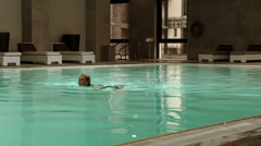 Attractive young blonde woman has a evening swimming in wellness pool Stock Footage