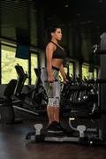 Mexican Woman Doing Exercise For Legs On Machine - stock photo