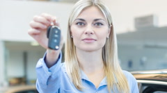 Young saleswoman is upholding the car keys Stock Footage