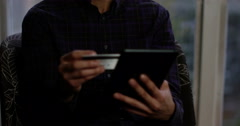 A young Asian man using a credit card with a digital tablet for online shopping. Stock Footage