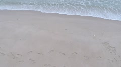 Stock Video Footage of Surf on sandy beach with footprints. Slow motion aerial video